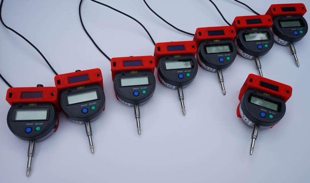 WLAN Messuhren zum Einbau in eine Messvorrichtung. 7 Messuhren zur Achsvermessung sind direkt in die Messvorrichtung eingebaut und werden über eine zentrale Stromversorgung mit Energie versorgt. Eine 8. Messuhr wird über den eingebauten LiIon-Akku auf der Rückseite versorgt. Alle Messuhren senden ihre Daten an den zentralen MQTT Server und können von diesem gesteuert ausgelesen werden.